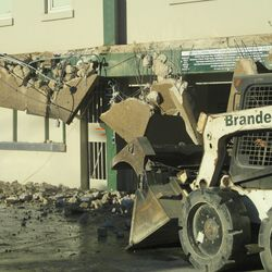 3:19 p.m. Work on the demolition stops, as one of the bobcats refuels -
