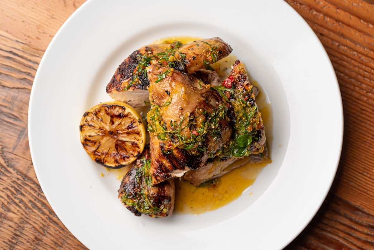 A grilled chicken with dark lines sits on a white plate.