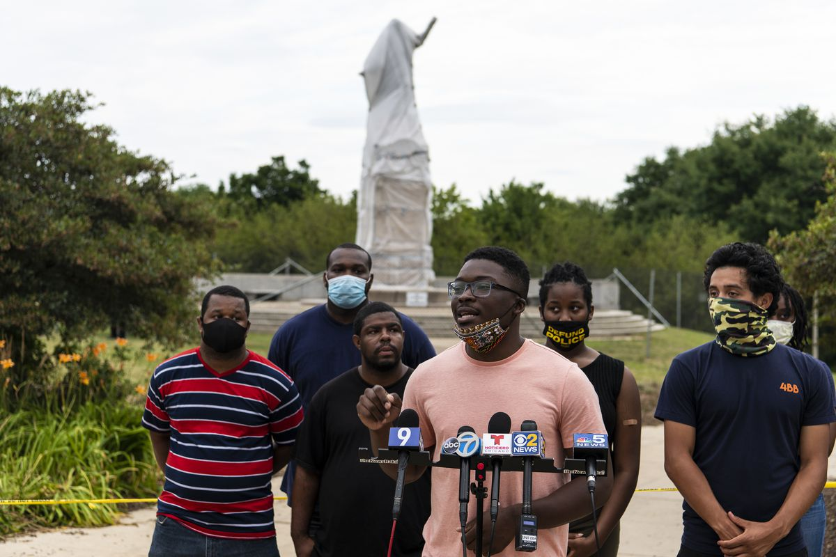 Activist Ja'Mal Green and representatives with Good Kids Mad City speak to reporters near the statue of Christopher Columbus in Grant Park in July.