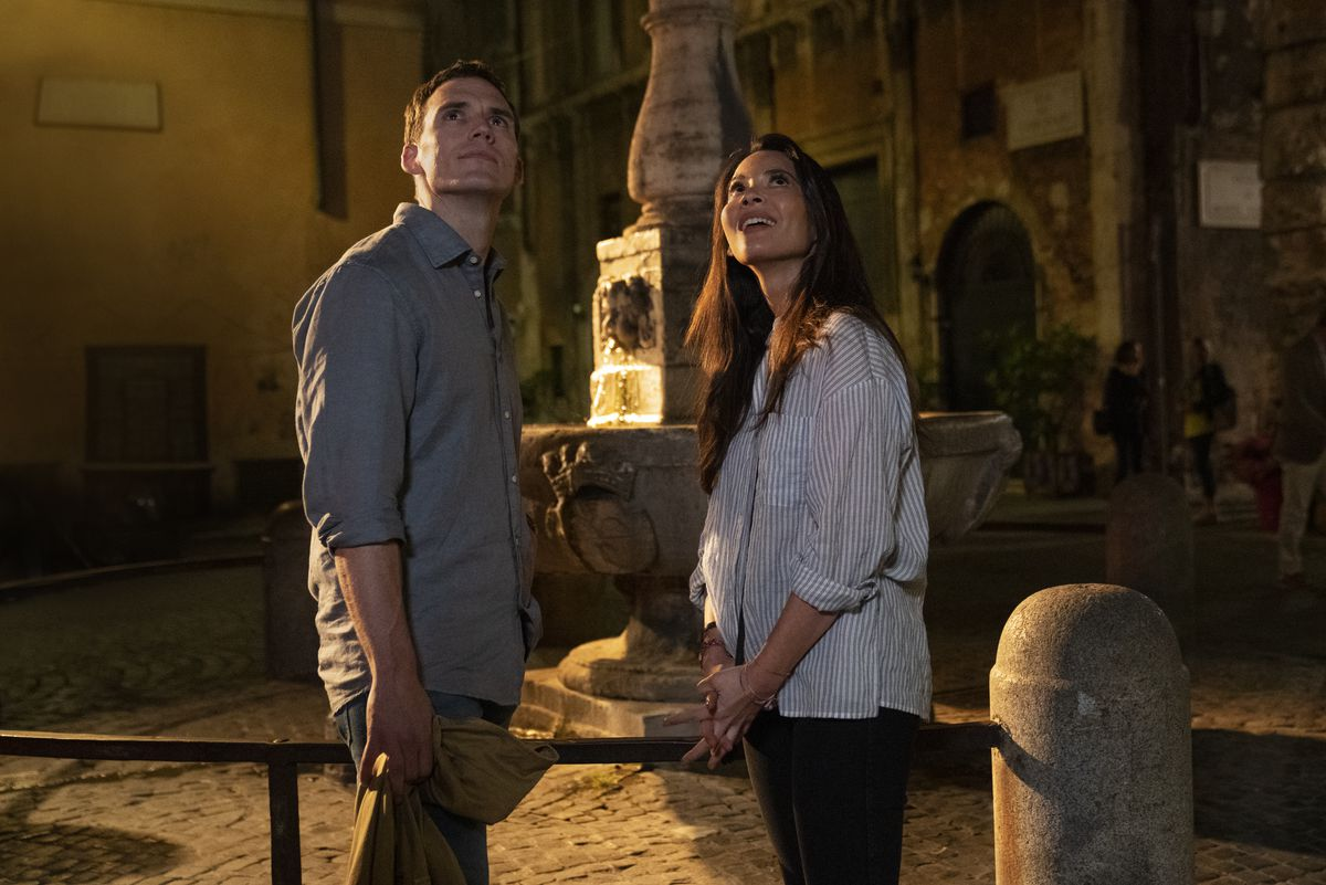 Sam Claflin and Olivia Munn, dressed as basically as humanly possible, stand outside in front of a Roman fountain, both staring upward and offscreen as though there's something interesting above them.