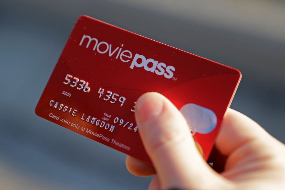 FILE - In this Jan. 30, 2018 file photo, Cassie Langdon holds her MoviePass card outside AMC Indianapolis 17 theatre in Indianapolis. The startup that lets customers watch a movie a day at theaters for just $10 a month, is limiting new customers to just f