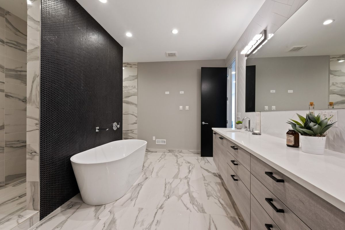 A tub against a black tiled accent wall which leads to a double shower. There is a long white countertop vanity with grey drawers.