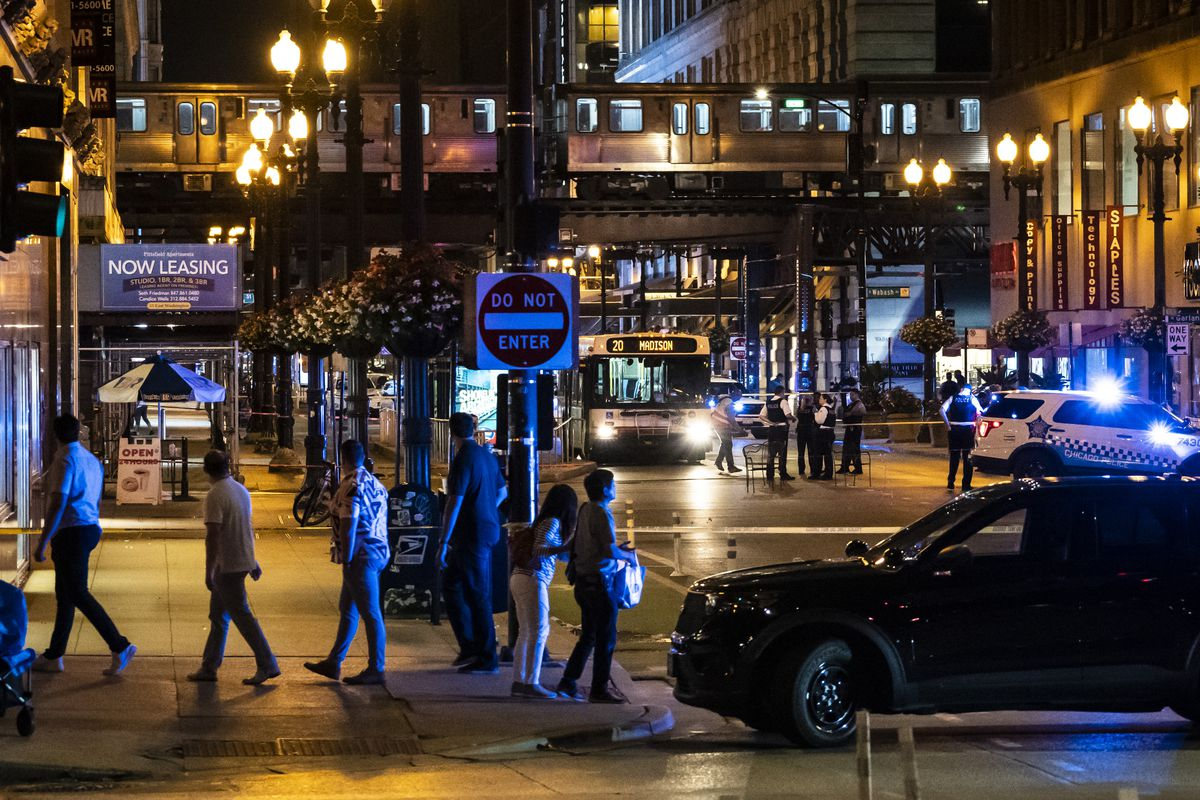 Passersby watch as Chicago police investigate after a CTA bus driver was shot Saturday night in the first block of East Washington Avenue in the Loop.