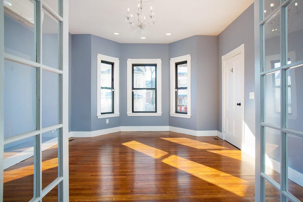 French doors opening into an empty room with a bay window.
