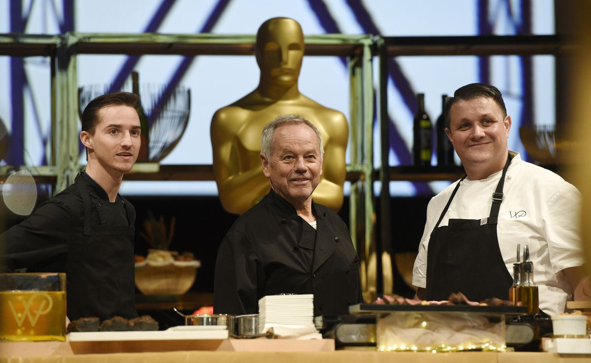 """Chef Wolfgang Puck (center) is flanked by his son Byron (left) and Eric Klein, vice president of culinary at Wolfgang Puck Catering, appear at the press preview for the 91st Academy Awards Governors Ball in Los Angeles in 2019. A new four-part documentary series, """"The Event,"""" shows the intense planning and details that go into high-profile catering."""