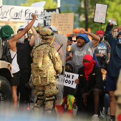 A large group of demonstrators yell at a National Guardsman and police officers between the Salt Lake City Library and the Public Safety Building on Monday, June 1, 2020.