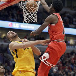 Chicago Bulls guard Justin Holiday, right, dunks against Utah Jazz center Rudy Gobert during the first half of an NBA basketball game Wednesday, Dec. 13, 2017, in Chicago. (AP Photo/Nam Y. Huh)