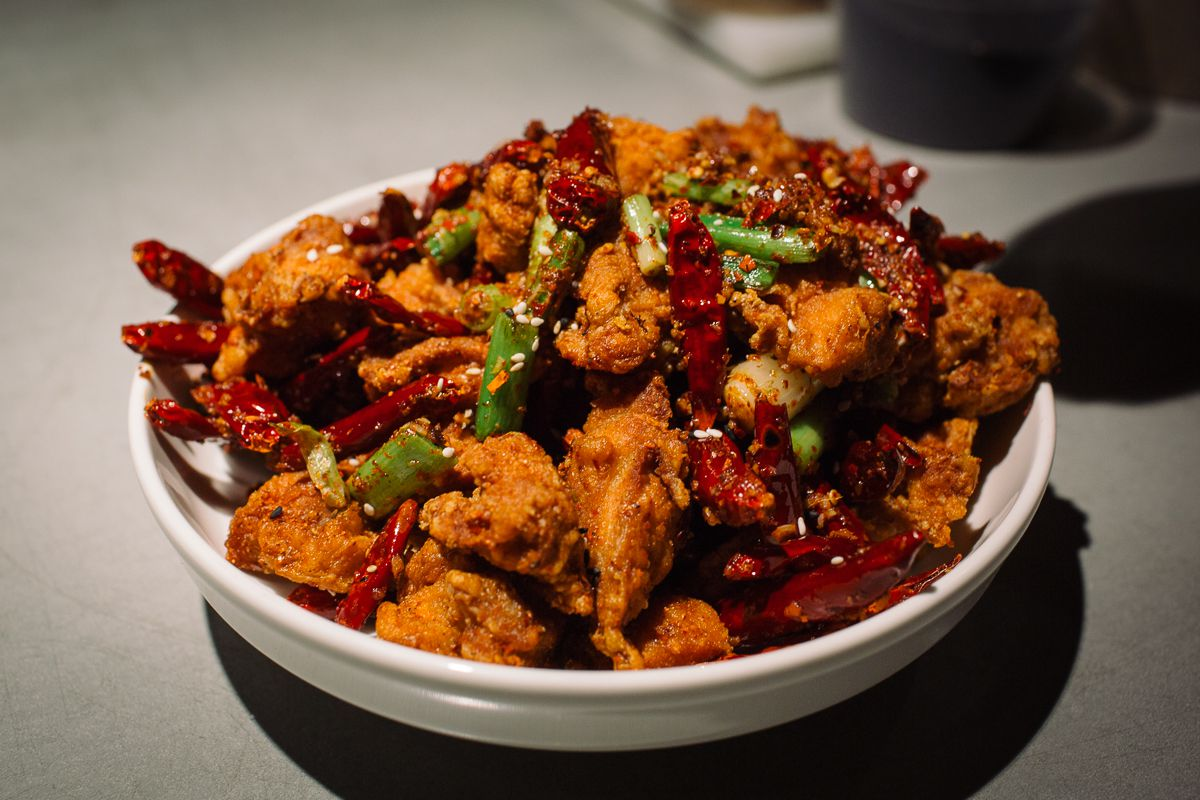 Bowl of Chinese fried chicken with chilies and scallions