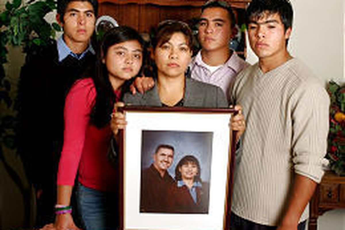 Alma Armendariz, center, poses with a photograph of her late husband, Aniceto, and her children: 18-year-old Joel, left, 13-year-old Karevi, 18-year-old Josue and 21-year-old Hector. He and Alma were returning from Mass when he was shot.