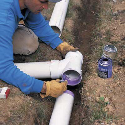 Glueing a sanitary T-fitting to the pipe end and the other end of its trench.