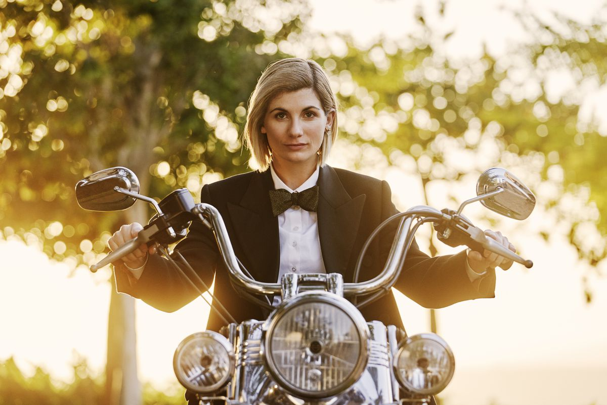 Jodie Whittaker as the Doctor in season 12 of the revived Doctor Who, riding a vintage motorcycle and wearing a blazer and bow tie.
