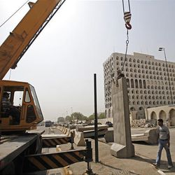 Workers place concrete blast walls in front of the Iraqi foreign ministry in Baghdad, Iraq, Saturday. Iraqi Foreign Minister Hoshyar Zebari said Saturday that those who carried out bombings that targeted government buildings in the Iraqi capital received help to pull off the attacks, possibly from Iraqi security forces.