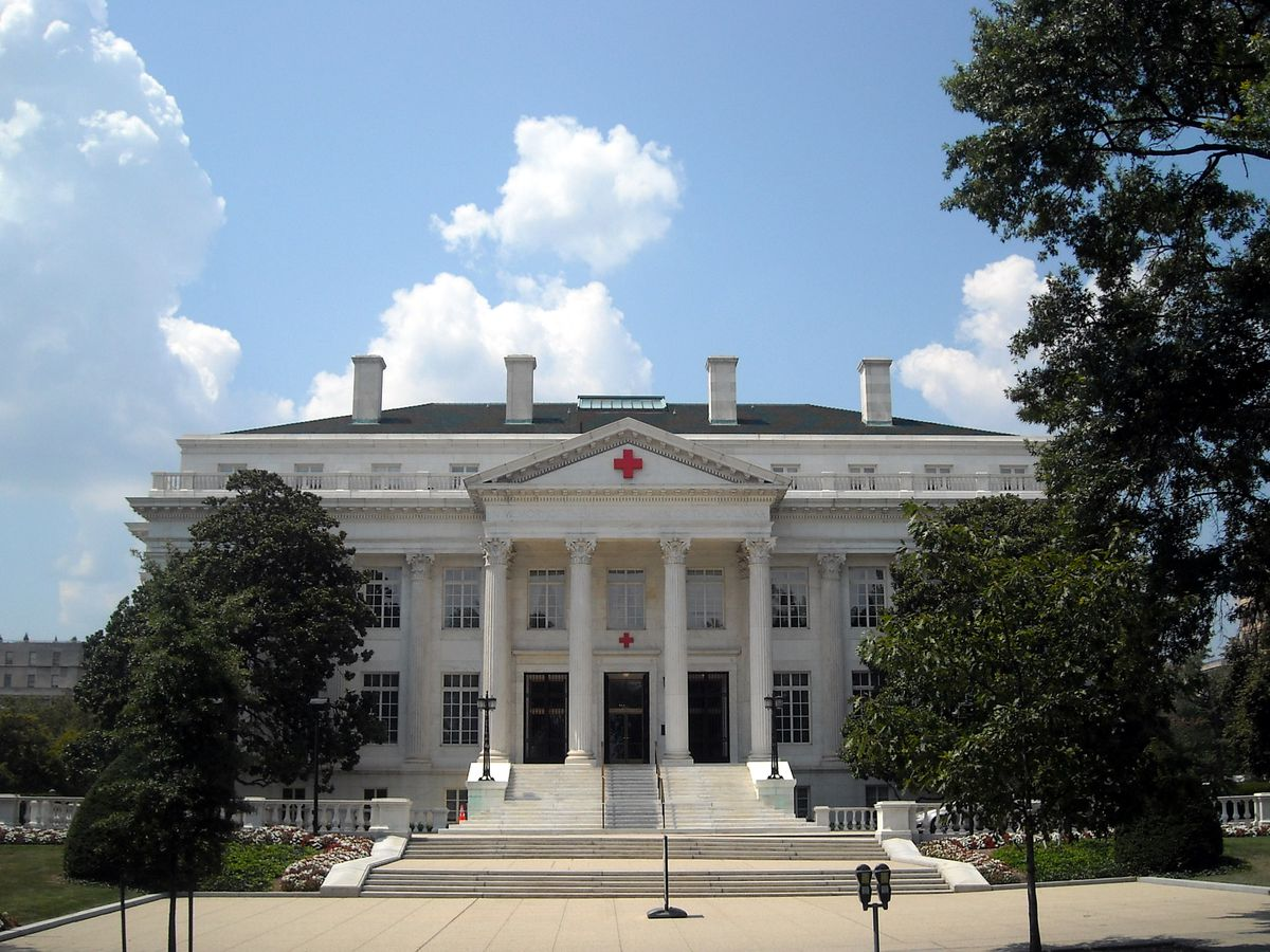 The exterior of the American Red Cross Headquarters in Washington D.C. The facade is white with columns.