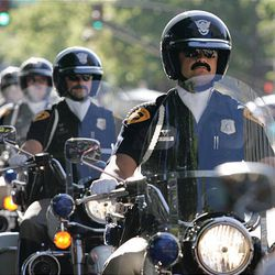 Salt Lake City police officers ride in the Days of '47 Parade in Salt Lake City with fake mustaches Saturday.