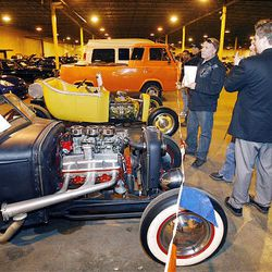 Sam Christensen, right, looks at the '31 vintage hot rod he just bought at the U.S. marshals auction Thursday. The marshals held an auction to sell off the $6 million worth of cars, boats and motorcycles of Jeffery Mowen, who is accused of operating a Ponzi scheme.