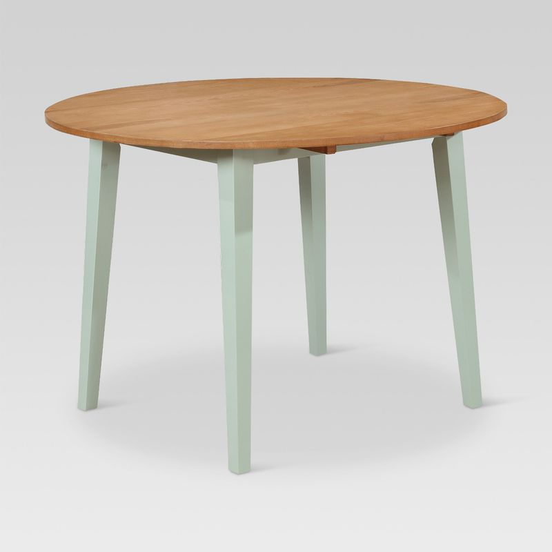A round table with light wood top and four squared mint green legs.