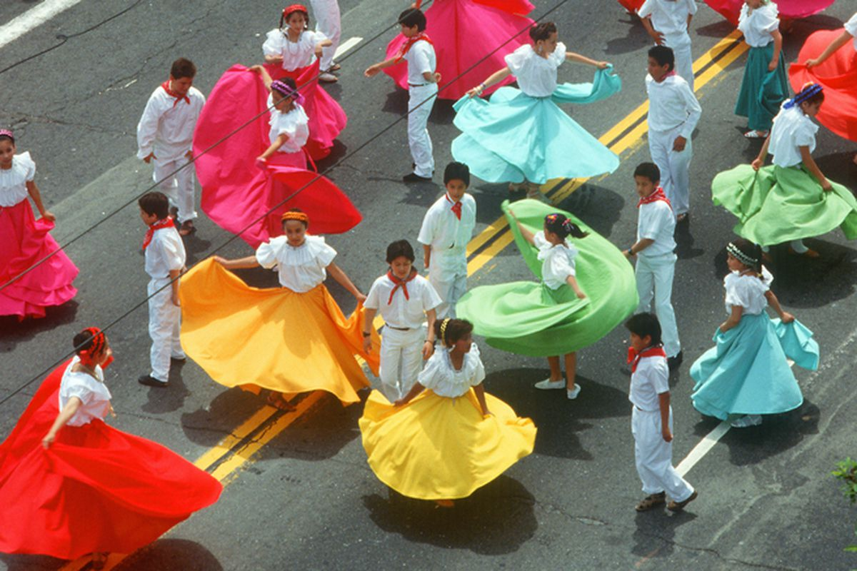 Dancers in colorful dresses in a Cinco de Mayo parade.
