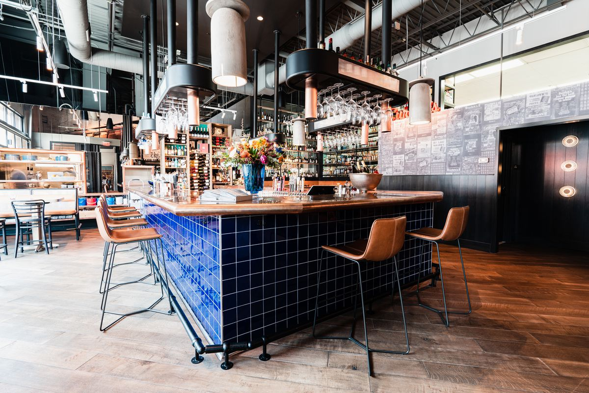 A corner view of the blue tiled bar with the low profile leather seats positioned around it.