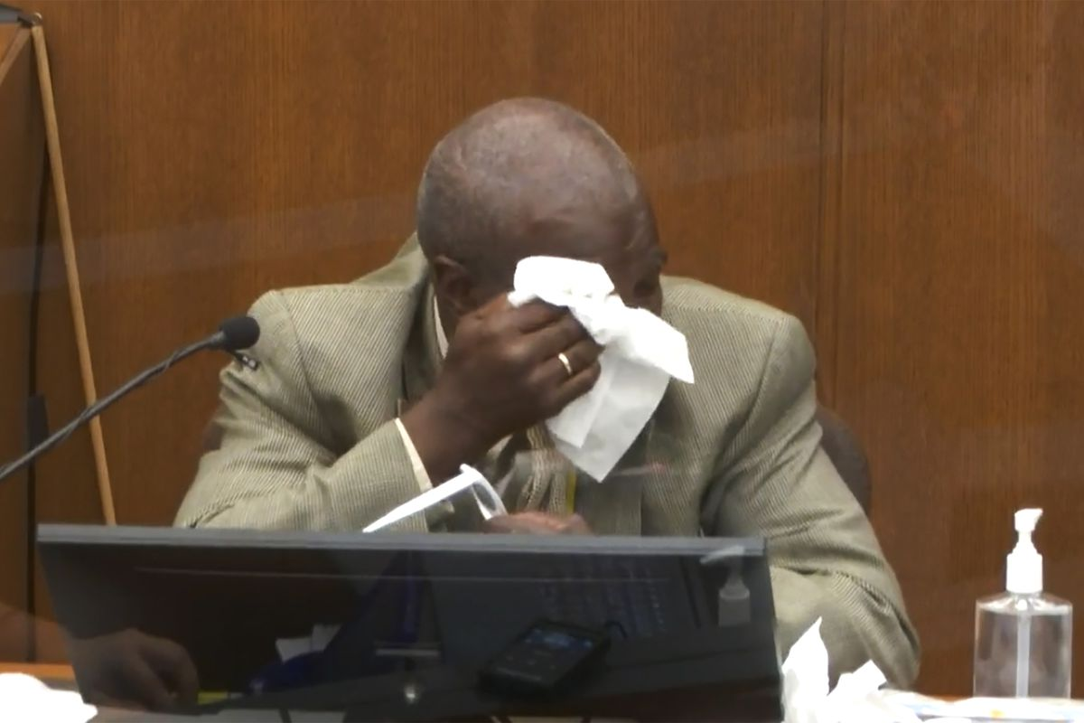 McMillian, a bald Black man in a tan suit, shirt, and tie, wipes tears from his eyes as he sits on the witness stand.