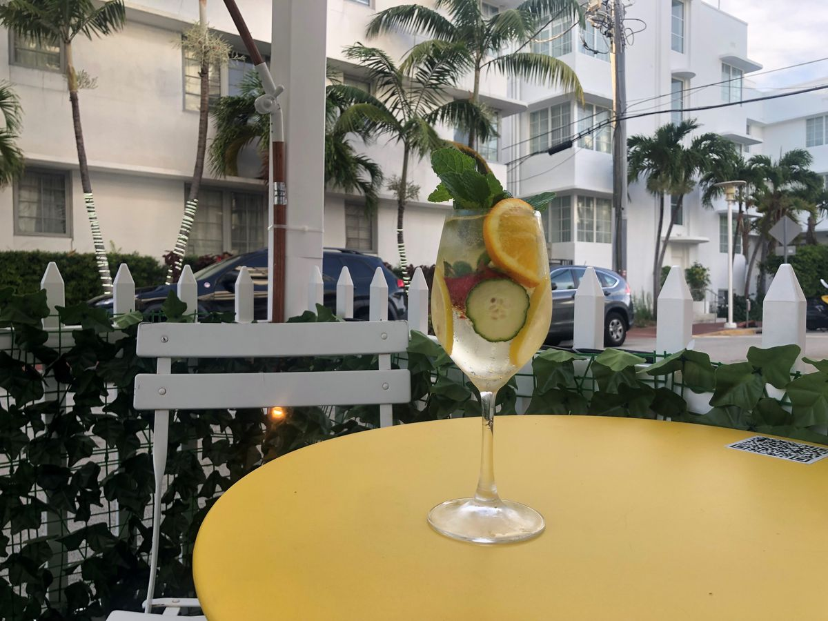 A clear cocktail in a wine glass filled with cucumber and orange slices on an outdoor table with views of palm trees