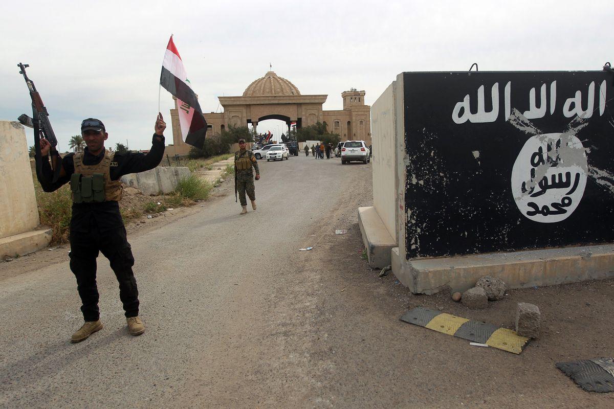 A Shia militia fighter celebrates the liberation of Tikrit.