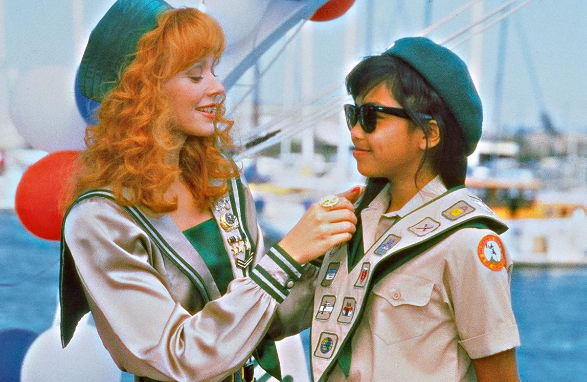Shelly Long helps a scout with her badge in a screenshot from Troop Beverly Hills