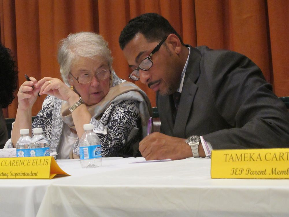 Chancellor Carmen Fariña huddles with District 17 Superintendent Clarence Ellis at a town hall meeting at M.S. 61.