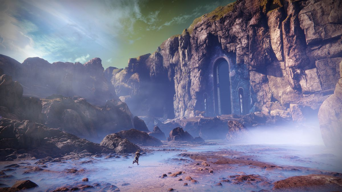 Destiny 2: Forsaken - a lone Guardian running toward a door cut into a rock face in the Dreaming City