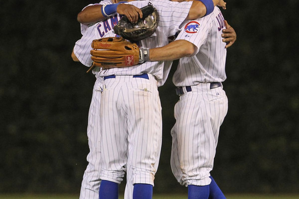 Tony Campana, Marlon Byrd and Reed Johnson of the Chicago Cubs hug after a win over the Washington Nationals at Wrigley Field on August 10, 2011 in Chicago, Illinois. The Cubs defeated the Nationals 4-2. (Photo by Jonathan Daniel/Getty Images)