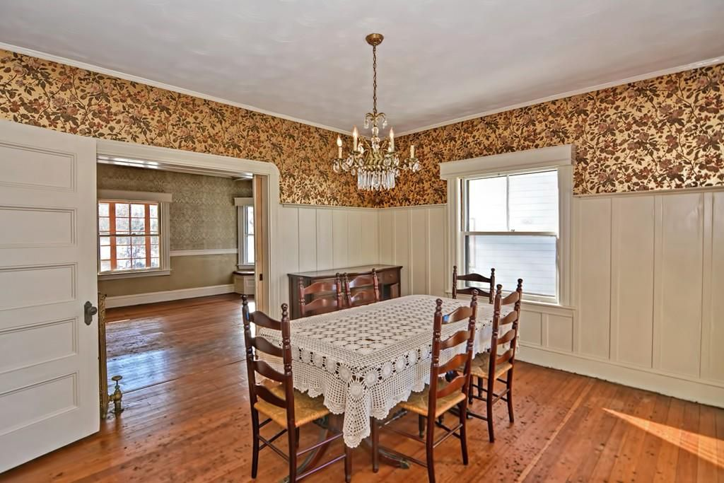 A dining room with a table and chairs, and there's a chandelier above the table and a door leading off the room.