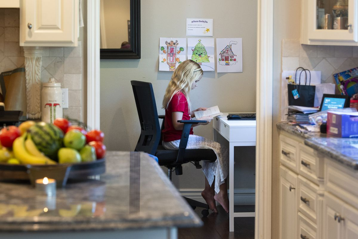 A child sits at a desk in an alcove off the kitchen in her house, looking at a book.