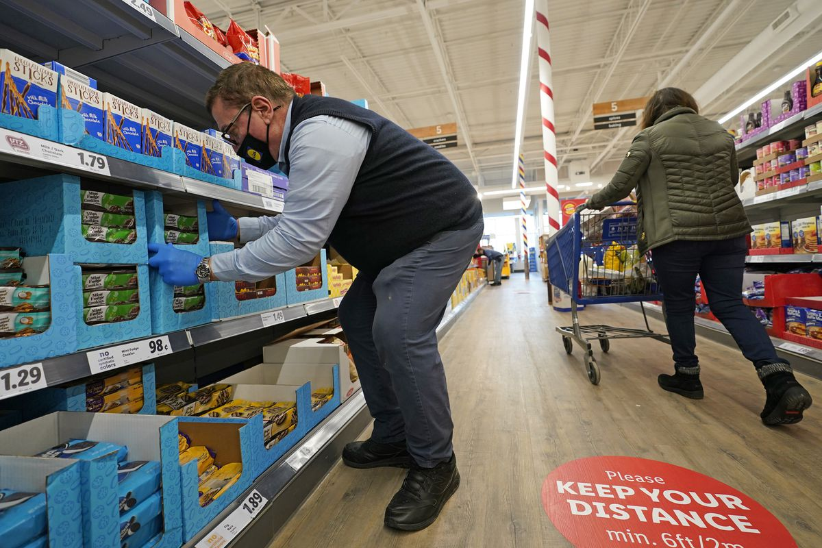 In this Thursday, Feb. 4, 2021 photo, grocery supervisor Joseph Lupo, left, arranges cookies in the shelves at the Lidl food market in Lake Grove, N.Y., where he works after getting the first dose of the COVID-19 vaccination earlier in the day.