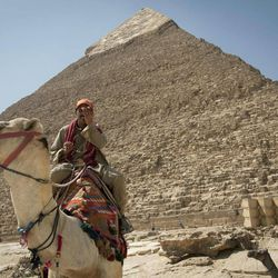 In this Thursday, Sept. 27, 2012 photo, a tour guide sits on his camel as he waits for clients next to the Giza pyramids, near Cairo, Egypt. The Egyptian demonstrations against an online film that was produced by a U.S. citizen originally from Egypt and denigrates the Prophet Muhammad were part of a wider explosion of anger in Muslim countries. They happened near the U.S. Embassy, far from the pyramids of Giza on Cairo's outskirts, and a lot further from gated Red Sea resorts, cocoons for the beach-bound vacationer. Yet the online or TV images _ flames, barricades, whooping demonstrators _ are a killjoy for anyone planning a getaway, even though the protests have largely subsided. Tour guides in Egypt say tourist bookings are mostly holding, but they worry about a dropoff early next year, since people tend to plan several months ahead.