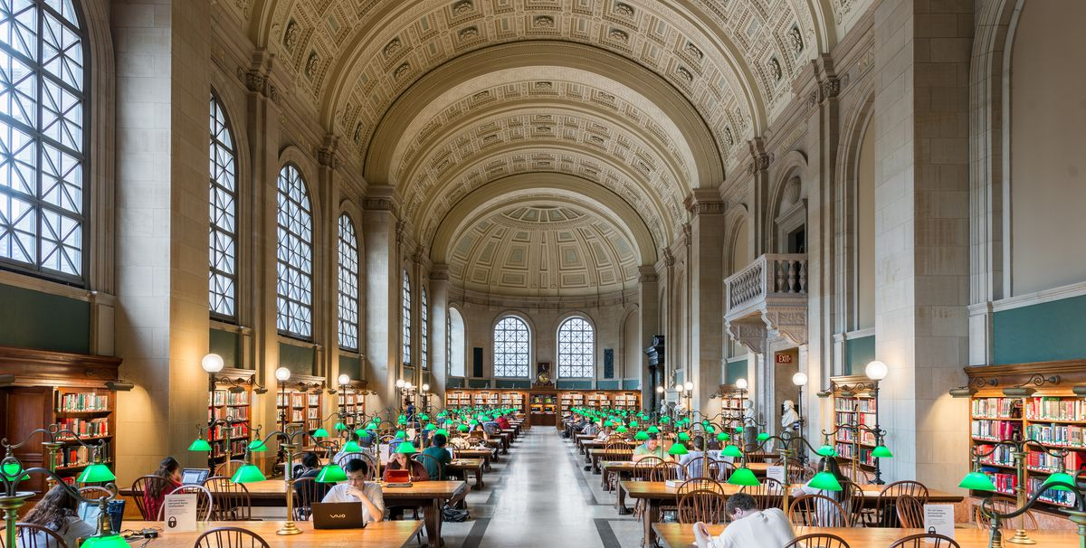 The interior of a room in the Boston Public Library.  The ceiling is domed with carved tiles. There are many tables and chairs. There are bookshelves with many books on the shelves.