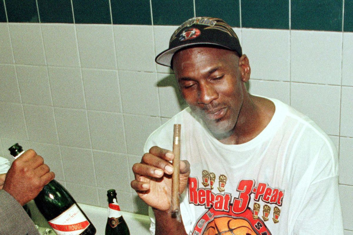Michael Jordan enjoys a cigar after the Bulls beat the Jazz in Game 6 of the 1998 NBA Finals. It was his sixth title.