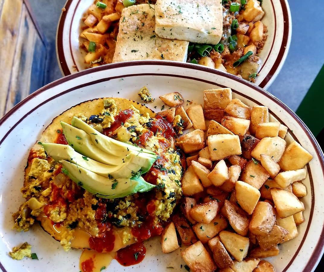 A plate of spiced tofu, black beans, and avocado on a tostada shell nestled beside potato homefries in the foreground, and a plate of homefries, green onions, and tofu slabs in the background.