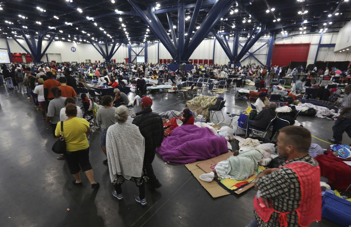 People line up for food as others rest at the George R. Brown Convention Center that has been set up as a shelter for evacuees escaping the floodwaters from Tropical Storm Harvey in Houston on Tuesday. | LM Otero/Associated Press