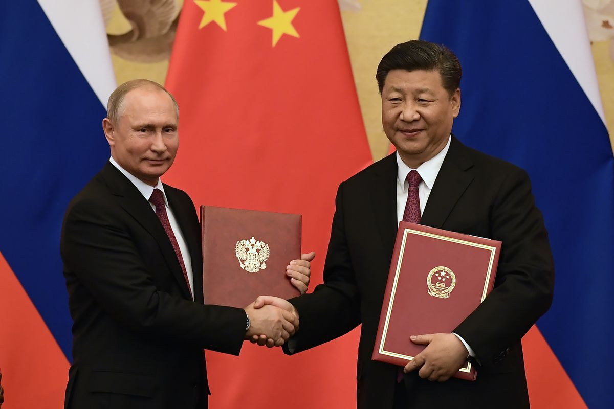 Chinese President Xi Jinping congratulates Russian President Vladimir Putin after presenting him with the Friendship Medal in the Great Hall of the People on June 8, 2018, in Beijing, China.