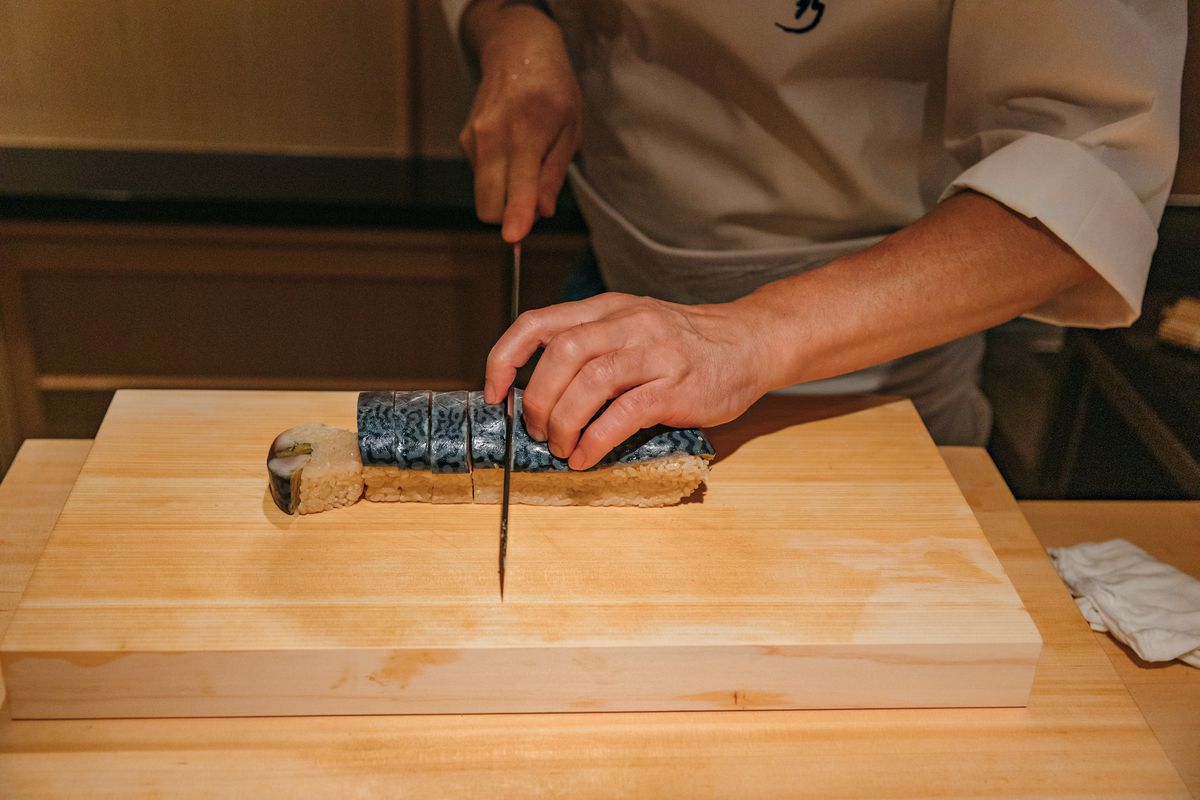 A chef cuts through sushi on rice on a wooden cutting board.