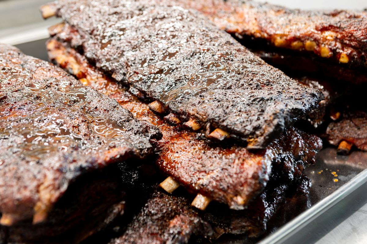 A stack of smoked spareribs, glistening and well blackened