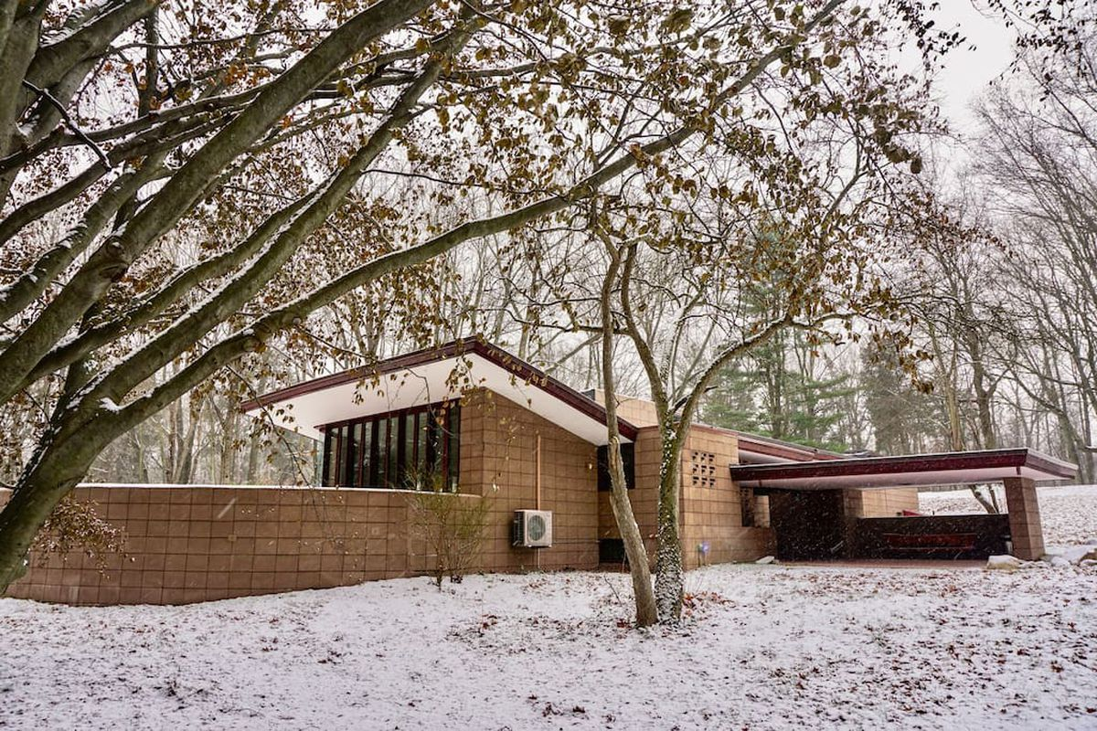 Mason-block home with low roof and carport amid snowy landscape.