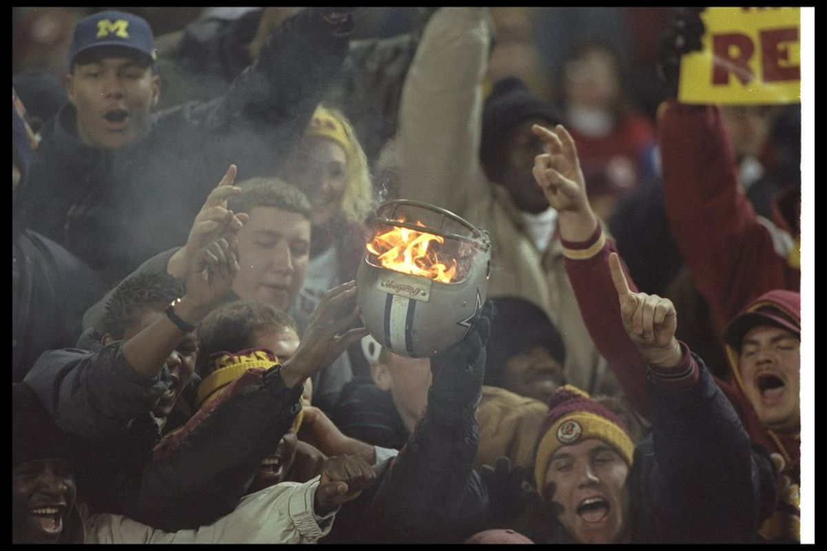 22 Dec 1996: Washington Redskins fans set fire to a Dallas Cowboys helmet during a game at RFK Stadium in Washington, D. C. The Redskins won the game, 37-7. Credit: Doug Pensinger /Allsport