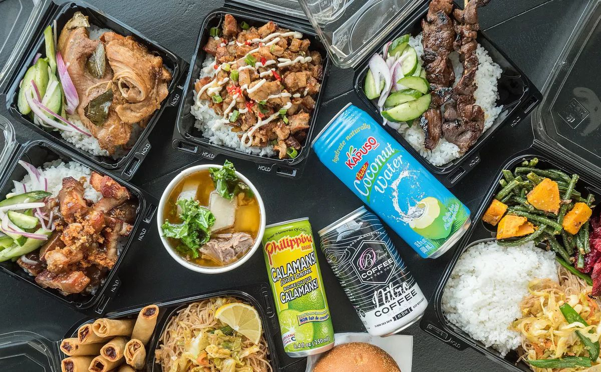 An overhead shot of Big Boi food, Filipino classics with roast meat and rice and drinks.