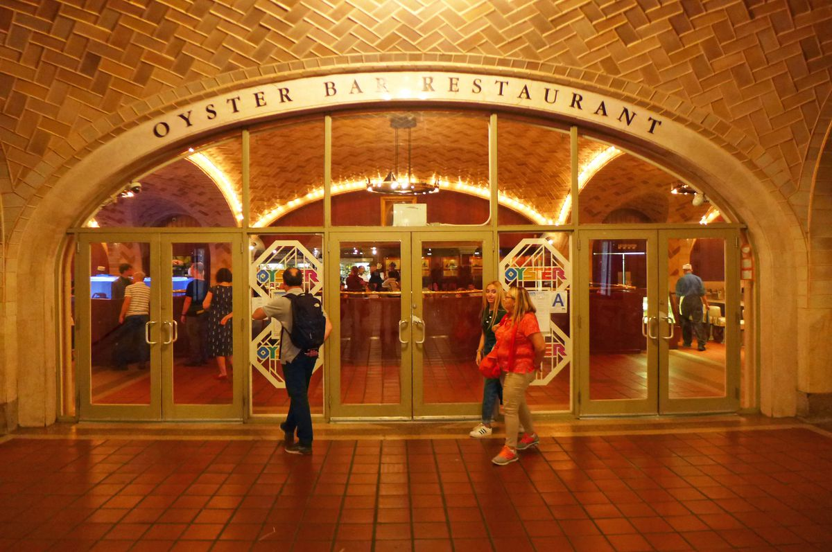 Arched entrance of the restaurant with a few people milling around in front...