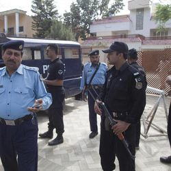 Pakistani police officers secure the area outside the house where Osama bin Laden's family are being detained in Islamabad, Pakistan, on Monday, April 2, 2012 in Islamabad, Pakistan. The lawyer for Osama bin Laden's family says a Pakistani court has convicted his three widows and two of his daughters on charges of illegally living in Pakistan and sentenced them to 45-days in prison.
