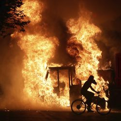 A man on a bike rides past a city truck on fire outside the Kenosha County Courthouse in Kenosha, Wis., on Sunday, Aug. 23, 2020. Kenosha police shot a man Sunday evening, setting off unrest in the city after a video appeared to show the officer firing several shots at close range into the man's back.