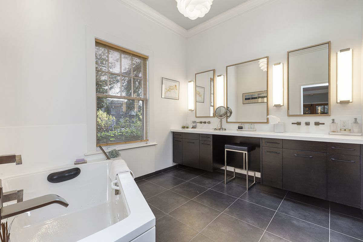 A large bathroom has dark gray tiles, a long counter with two sinks, gold mirrors, and a white bathtub.