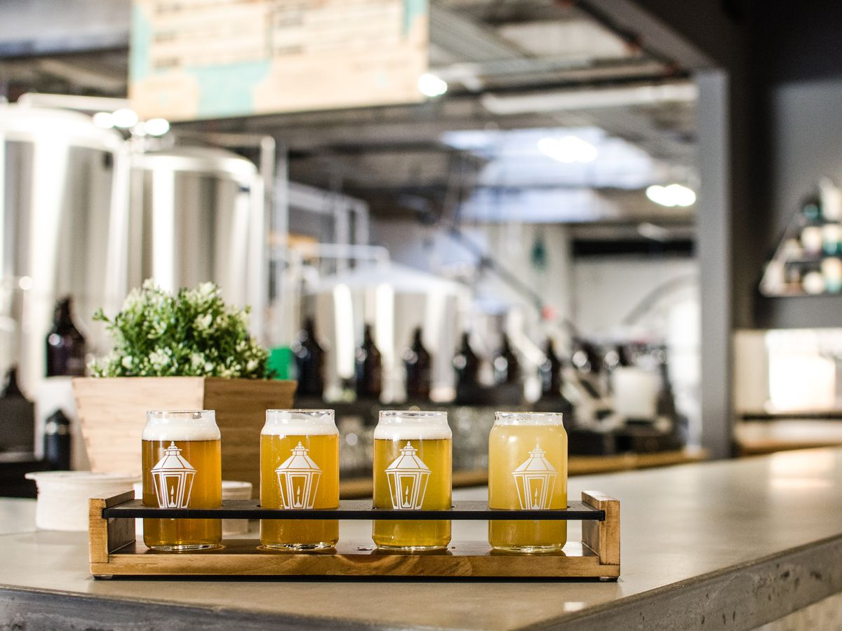 A flight of beer in Lamplighter Brewing-branded glasses sits on a bar, with brewing equipment visible in the background