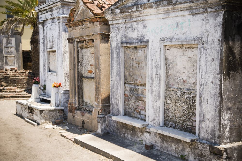 A cemetery with above ground mausoleums. All of the mausoleums are decayed.