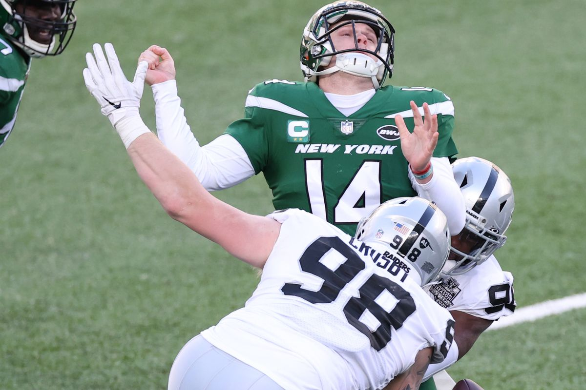 Sam Darnold #14 of the New York Jets fumbles as he is sacked by Clelin Ferrell #96 of the Las Vegas Raiders during the first half at MetLife Stadium on December 06, 2020 in East Rutherford, New Jersey.